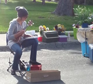 a teenager playing music at a farmer's market
